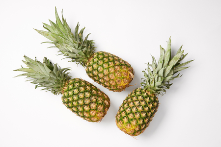 top view of tasty exotic pineapples on white background
