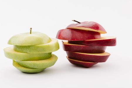 Rodajas de manzanas deliciosas doradas y rojas sobre fondo blanco.