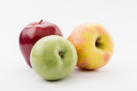 fresh red, green and yellow apples on white background