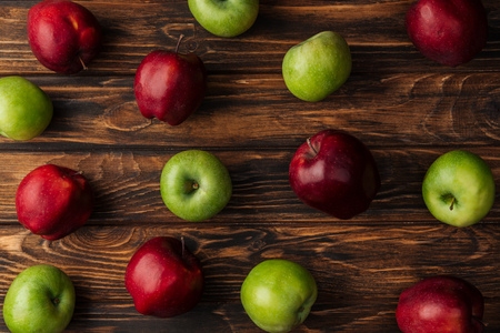 top view of ripe red and green apples on wooden table