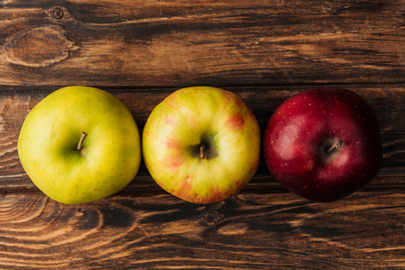 top view of row of ripe multicolored apples on wooden table Фото со стока