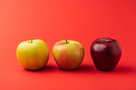 row of three ripe multicolored apples on red background Banco de Imagens