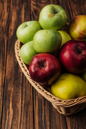 wicker basket with tasty multicolored apples on wooden table Stock Photo