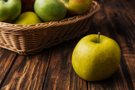 golden delicious apple with fruit wicker basket at background