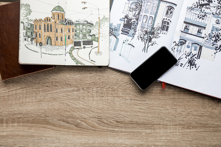 top view of drawings in albums and smartphone on wooden background Stok Fotoğraf