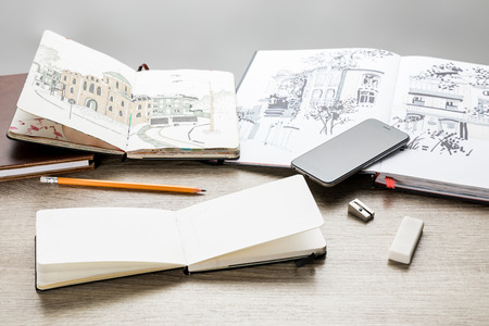 selective focus of drawing albums, drawing utensils and smartphone on wooden table