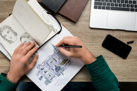 top view of mans hands drawing in album on wooden  table next to smartphone and laptop