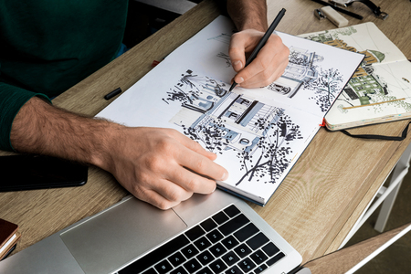 selective focus of mans hands drawing in album on wooden table next to  utensils Stockfoto