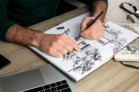 selective focus of mans hands drawing in album on wooden table next to laptop Banco de Imagens