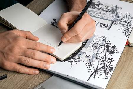 selective focus of mans hands drawing in notebook on wooden table next to album