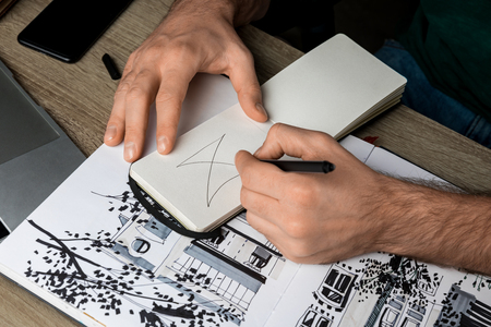 selective focus of mans hands drawing in notebook on wooden table next to album and gadgets