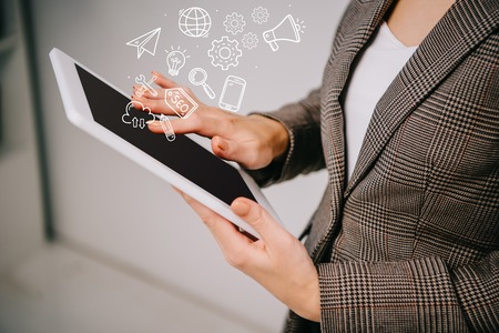 cropped view on businesswoman using and touching digital tablet with seo icons Imagens