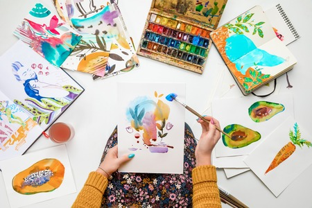 top view of woman holding drawing on knees and painting in it with watercolors paints while surrounded by colored pictures