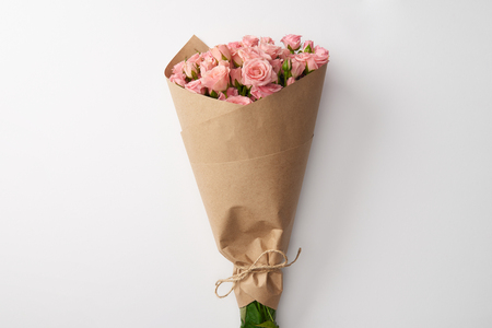 bouquet of beautiful pink roses wrapped in craft paper on grey Imagens