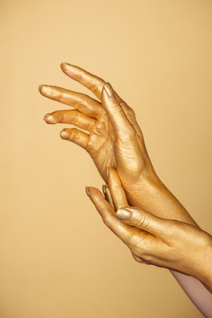 partial view of female painted hands isolated on gold 写真素材