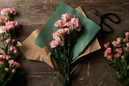 top view of beautiful pink flowers with craft paper and scissors on wooden surface