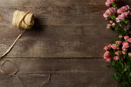top view of beautiful tender pink flowers and ribbon on wooden background