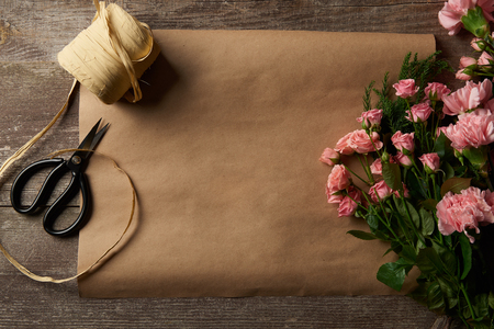 top view of beautiful pink flowers, scissors, ribbon and craft paper on wooden surface
