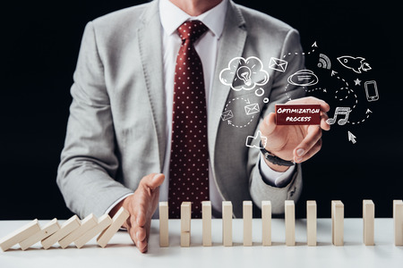 cropped view of businessman preventing wooden blocks from falling while holding brick with words optimization process, icons on foreground Banco de Imagens