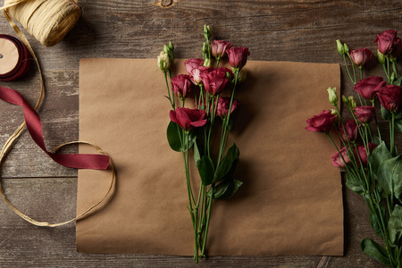 top view of beautiful red eustoma flowers on craft paper and ribbons on wooden surface