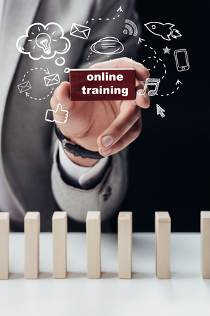partial view of man holding red brick with words online training isolated on black, icons on foreground