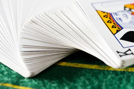 selective focus of horizontally spread out playing cards in deck on green poker table