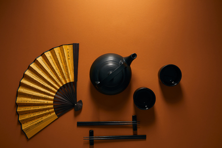 top view of black tea set, chopsticks and golden fan with hieroglyphs on brown Zdjęcie Seryjne