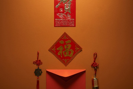 red envelope, hieroglyphs and traditional decorations on brown background, chinese new year concept Banque d'images - 116407398
