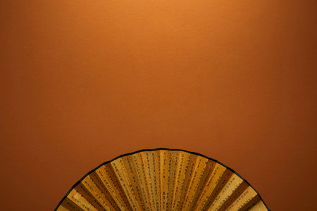 Top view of traditional golden Chinese fan with hieroglyphs on brown background