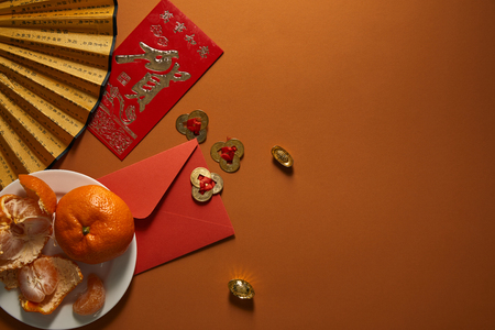 top view of tangerines on plate, fan with hieroglyphs, golden decorations and red envelope on brown background, chinese new year composition Banque d'images - 116591823