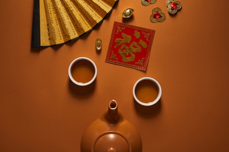 top view of tea set, fan with hieroglyphs and traditional chinese decorations on brown Banque d'images - 116593497