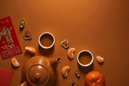 top view of tea set, tangerines and traditional chinese decorations on brown background 免版税图像