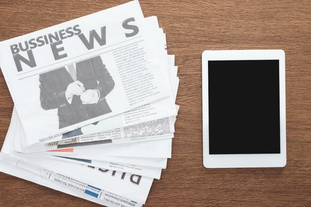 top view of tablet with blank screen and business newspapers on wooden tabletop