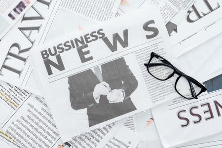 top view of business newspapers and eyeglasses on surface