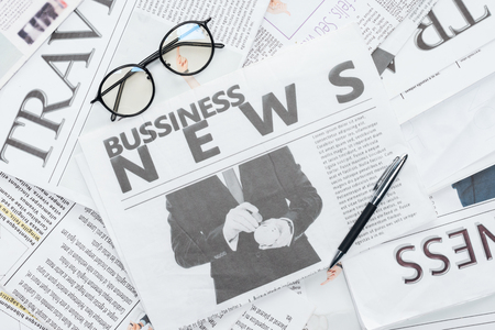 top view of eyeglasses and pen on business newspapers Banco de Imagens