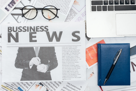 elevated view of eyeglasses, pen and notebook and laptop on newspapers