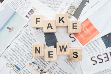 Vista superior de cubos de madera con palabras noticias falsas en periódicos Foto de archivo