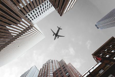 bottom view of skyscrapers and airplane in cloudy sky in new york city, usa Zdjęcie Seryjne