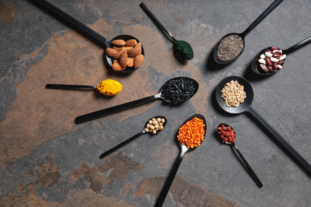 flat lay of spoons with superfoods, legumes and grains on table
