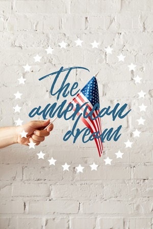 cropped image of man holding american flagpole against white brick wall with the american dream illustration Stockfoto