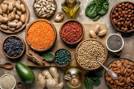 flat lay of legumes, superfoods and healthy ingredients on wooden board with rustic background Stock Photo
