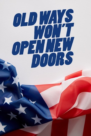 top view of united states of america flag and old ways wont open new doors quote on white surface