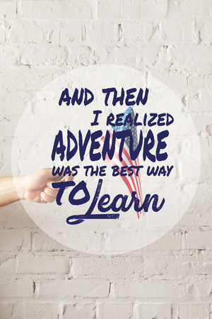 cropped image of man holding american flagpole against white brick wall with and then i realized adventure was the best way to learn quote 版權商用圖片 - 116407510