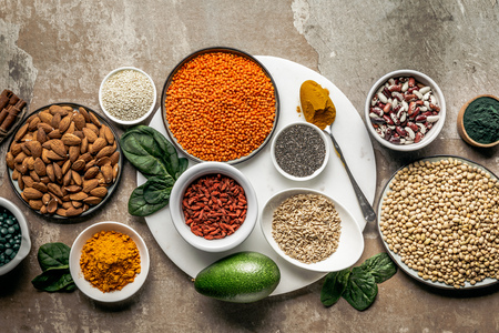 top view of superfoods, oat groats and legumes on textured rustic background