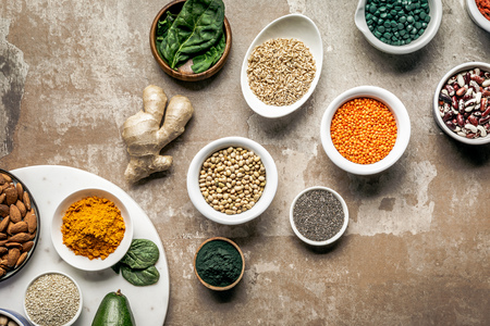 flat lay of superfoods, spices and legumes on textured rustic background Stockfoto