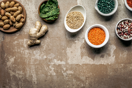 top view of legumes, ginger and spinach on textured rustic background with copy space