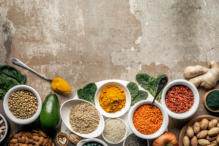 flat lay of superfoods and legumes on textured rustic background with copy space