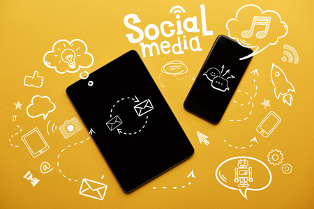 top view of digital tablet and smartphone with social media illustration on yellow background
