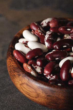 selective focus of raw swallow beans in wooden bowl Stockfoto
