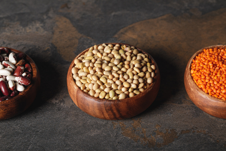 beans, soy and lentils in wooden bowls on table